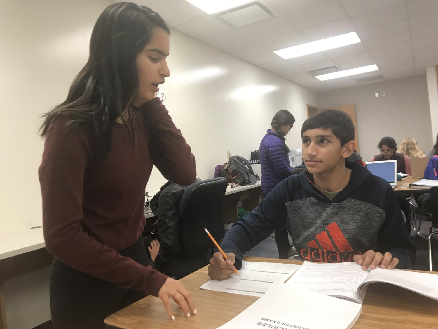 Sophomore Nimish Bhat helps out a DECA member during a roleplay practice session in SRT.
