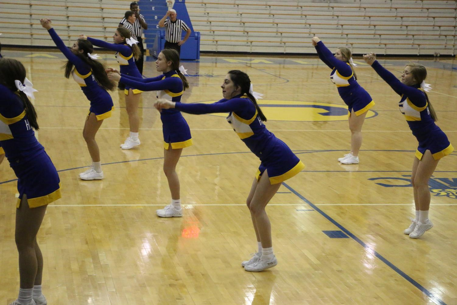 Winter Cheerleading team performs a cheer with various stunts at a women's basketball game. The cheerleaders performed this cheer during a time out to encourage the fans to cheer and because they were able to do stunts on the court.
