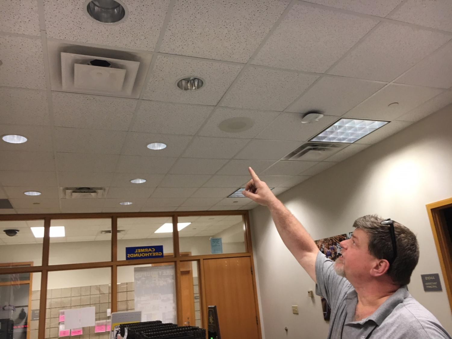 Maintenance worker Fred Napier points to a light in the activities office that went out earlier this week. This was one of many work orders that the maintenance staff has to look at on a daily basis.