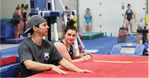 GYMNASTIC COMMITMENT: Senior and gymnasts Crossen talks to one of her coaches about her form and what to improve during her practice. Crossen said that her coaches helped her understand what each college and university had offered when they had started giving offers to her. She said she ended up committing later than most other gymnasts to keep her options open.