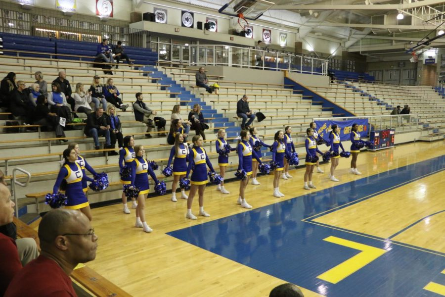 Winter Cheerleading cheers for the womens basketball team in the Eric Clark Activity Center. The team switched between facing the court to cheer on the basketball team and facing the crowd to get them to join in cheering for the basketball team.