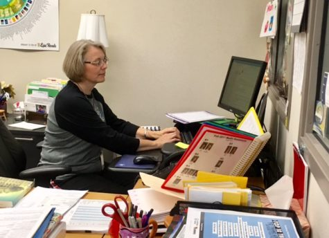 Terri Ramos, department chairperson for media and communications types on her computer. Ramos said the media center is always busy, but will be open during finals to support students.