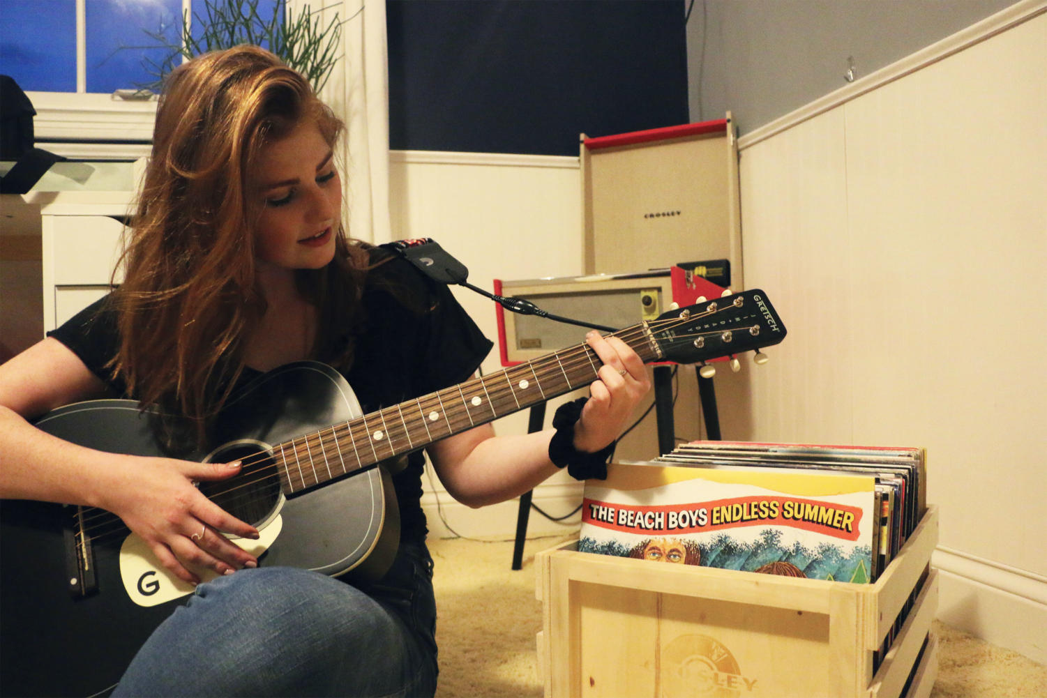 Sophomore Ella Carlson plays the guitar in  front of her vinyl collection and her record player. Carlson said she learned to play the guitar on her own last summer.