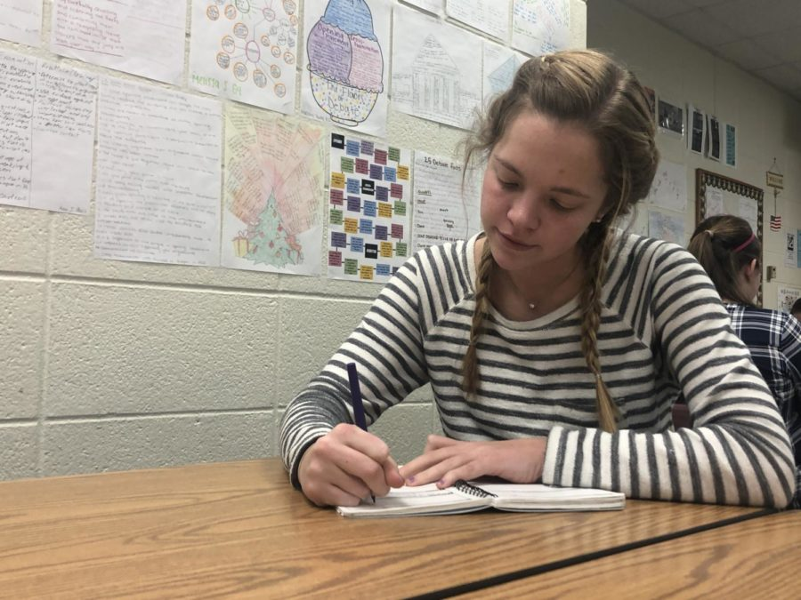 Anne Schuh, Best Buddies president and senior, works on homework during SRT. She said she is most excited for the upcoming Pacers game that the club will be attending.