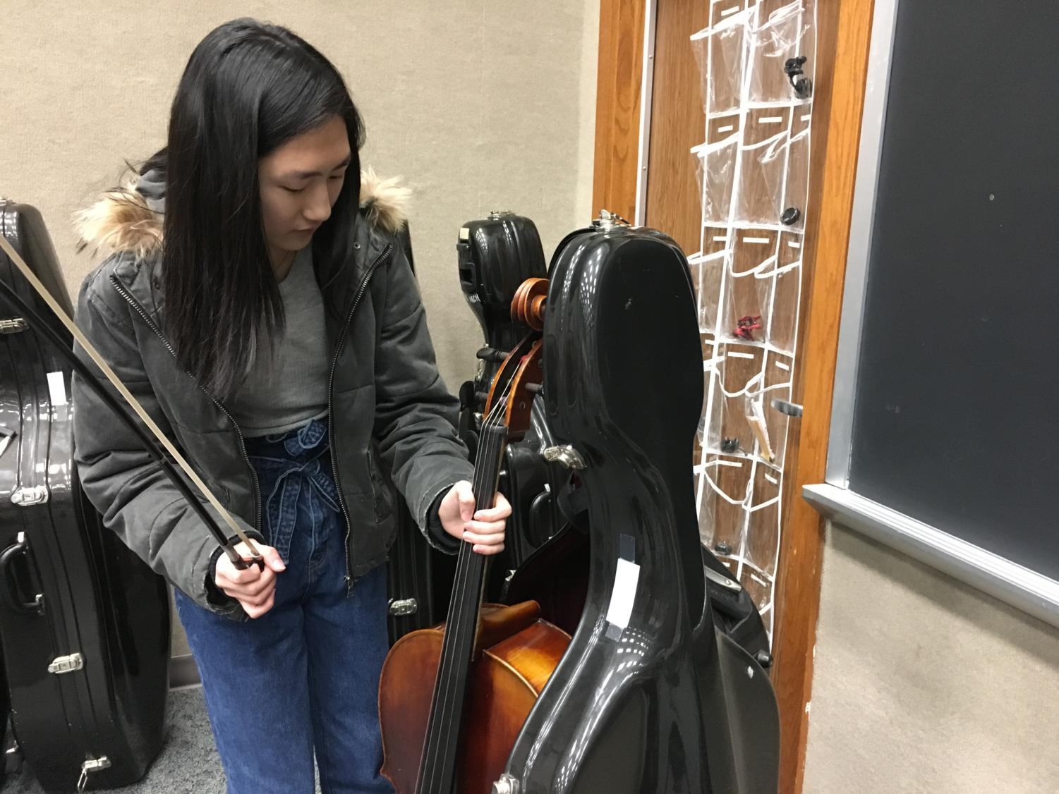 """Carol You, member of Symphony Orchestra and sophomore, unpacks her cello for an after school rehearsal. You had already practiced her chamber music in class in order to prepare for the upcoming chamber music concert on Jan. 30 but said she was looking forward to running through it with the band members during rehearsal. """"We practice (our chamber music) after school with the percussion, winds, and brass,"""" You said."""