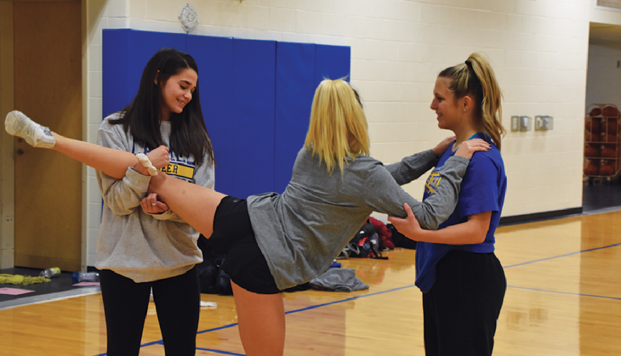 FRIEND STRETCH: Elie Anania and Veronica Light, gold winter cheerleaders and juniors, help Blair Wayman,  gold winter cheerleader and sophomore, stretch. Wayman stretched before stunting during practice.