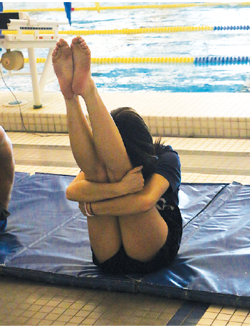 Flexibility Training: Jenna Springirth, winter cheerleader, diver and sophomore stretches at the start of practice. After stretching, she performed several dives focusing on specific skills each time.Springirth does both cheerleading and diving because of the similar movements involved in the two.