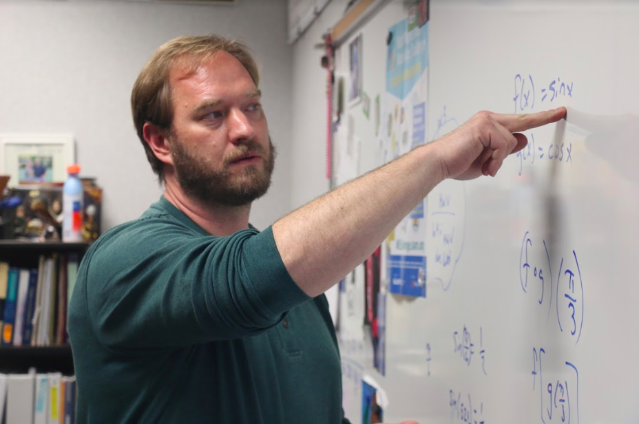 TEACHING TIME: Math teacher Peter Beck teaches his multivariable malculus class at the end of the day. He explained a problem to a student at the end of class to help them better understand the concept.