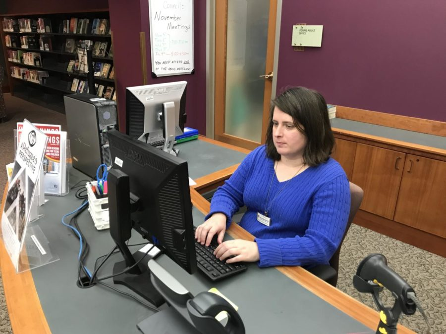 Jamie Beckman, young adult librarian at the Carmel Clay Public Library, works at the young adult section desk. Beckman and other library staff members will be working with the Teen Library Council to host the Yule Ball this Saturday.