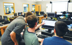 CODING CRACKDOWN: Evan Kenyon (center) and Joseph Paavola (left), Code for Change officers and seniors, work together on code. The club meets after school on Tuesdays.