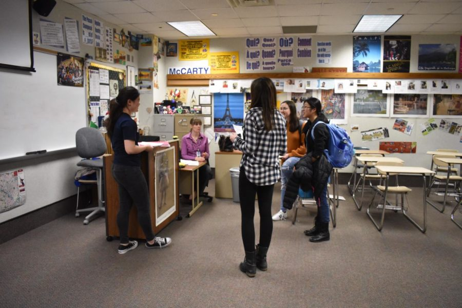 """Friends in French: French teacher Mrs. Schmitt talks with CHS French club members in her classroom on Jan. 15 after they turn in forms in order to go to the Congrès Competition on Feb 9. Angela Chen (right), french club member and sophomore, said that for the competition the club will """"go to another school and compete in some french related activities."""""""