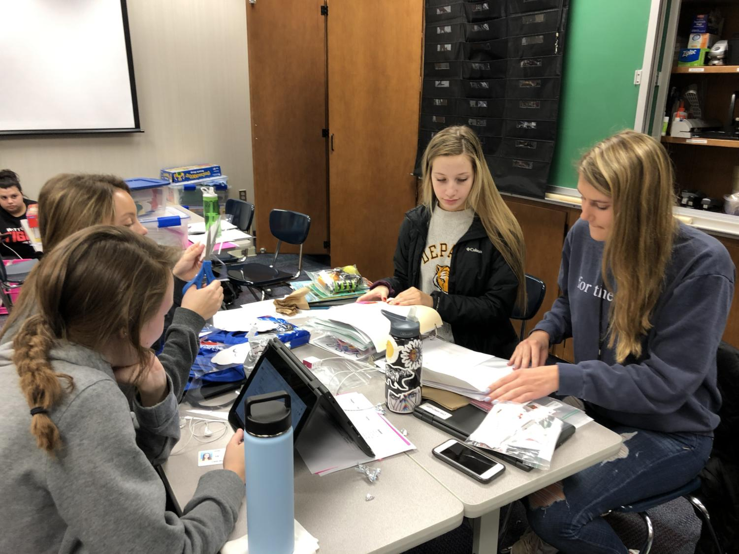 (Right to Left) Juniors Maddison Grave, Ellie Esrael, Aeryn Hopwood, and Livvie Miller work on teaching props to accompany their lesson plans during a G4 Kid's Corner class on Feb. 22, 2019.