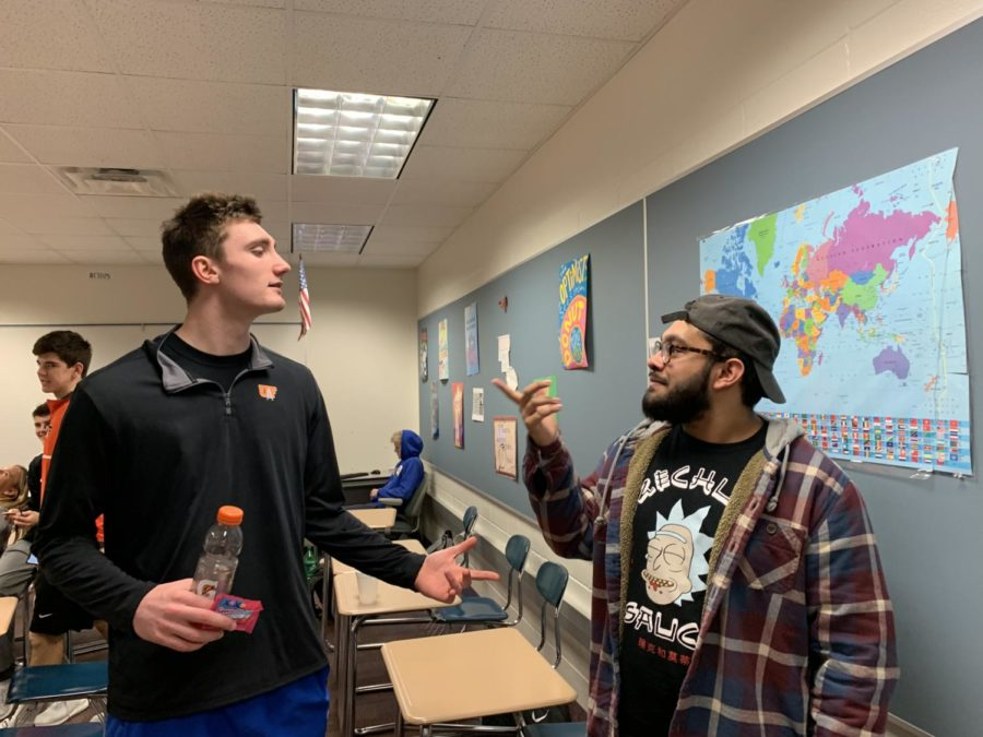 """Senior Christian Chacko (right) goes over some planned activities for the game with his fellow club members. """"Show out at the game on Friday versus Fishers,"""" Chacko said."""