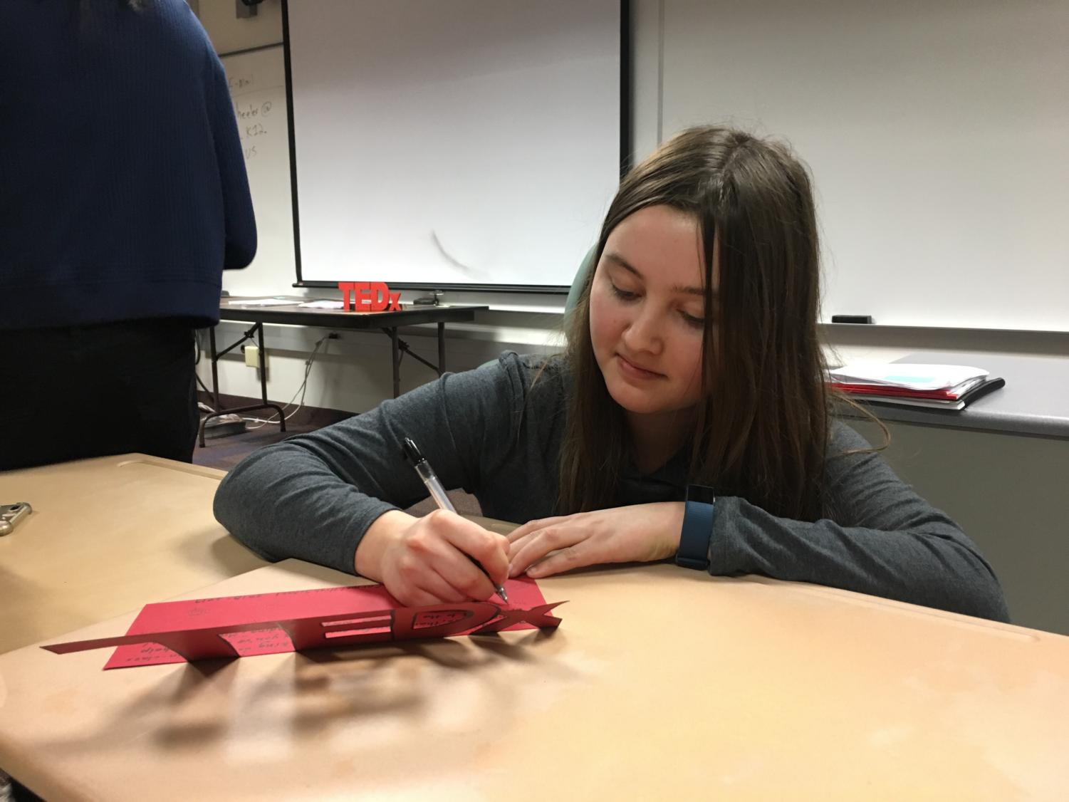 Ally Eaton, TEDx Event Planning committee head and senior, signs a thank you card for Allison Hargrove, former TEDx sponsor and social studies teacher. According to Selin Oh, TEDx president and senior, this card is a gesture to show Hargrove how great her impact on the club has been and how grateful the members have been for her support.
