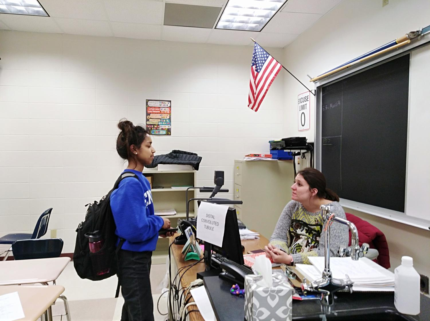 Sponsor and science teacher Alyssa Mastin talks with a senior Semanti Naiken about a Top Scholar nomination. Mastin said she often stays after school to talk with students or finish her work.
