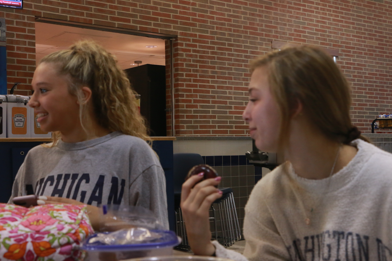"""Juniors and dancers Lexi Dungey (left) and Maddy Massa (right) have lunch together as team members. The girls try to balance school, dance and socialization. """"I use the time I have to get things done and bond with my teammates, who quickly become close friends,"""" Massa said."""