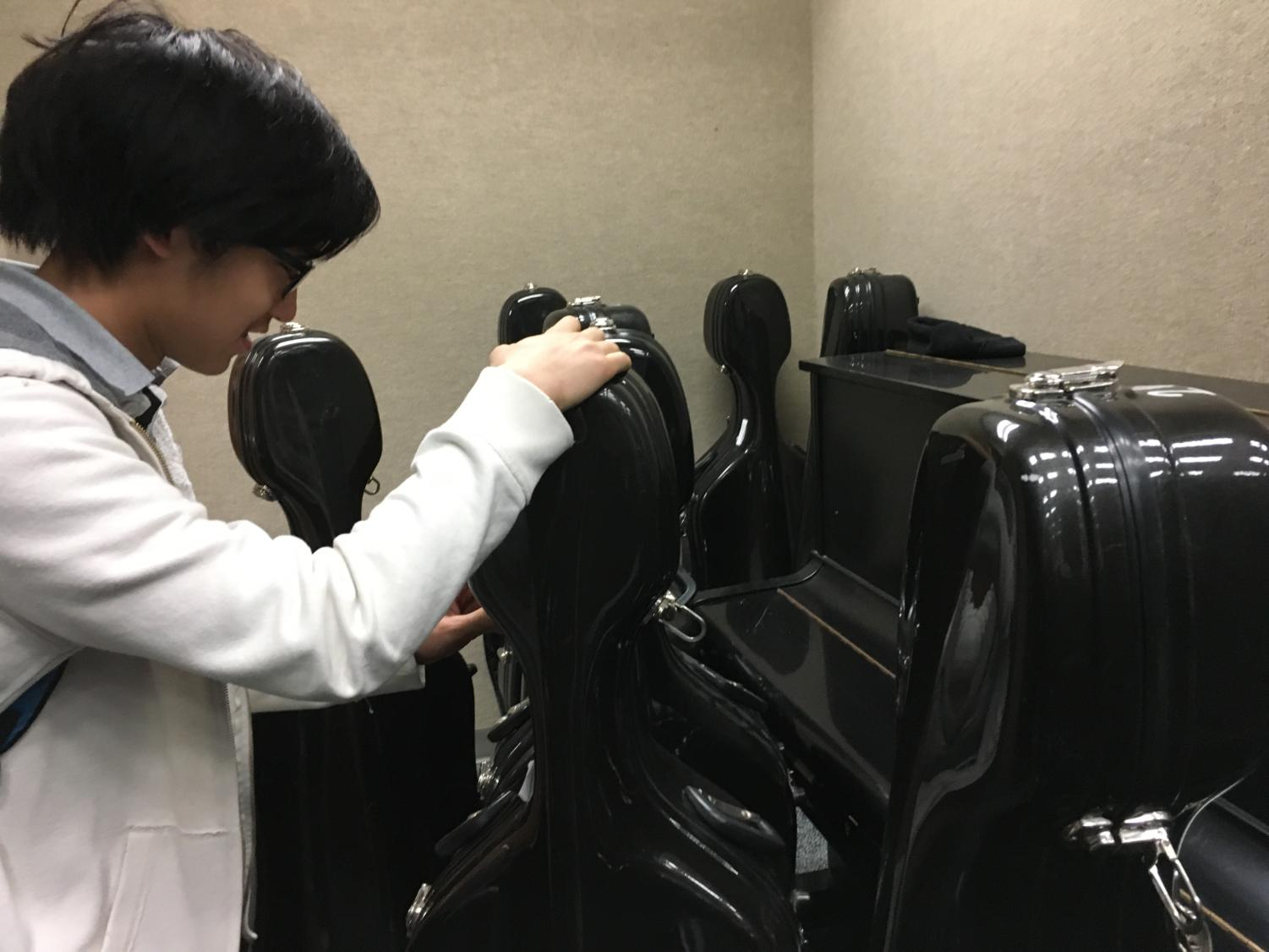 Noah Tan, member of Philharmonic Orchestra and sophomore, takes his cello out of its case before after school rehearsal. He said the main focus of his orchestra class for the past few weeks has been to prepare their chamber music and contest music.
