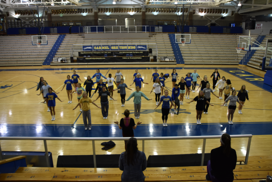 Winter cheer team practices a group cheer to perform at games. They were holding this pose to clean the move and make their cheer look more unison.