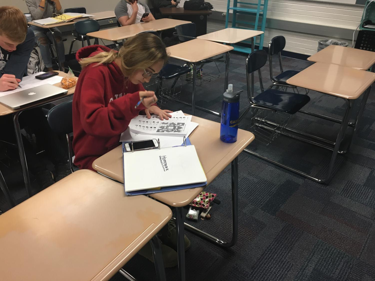 "Riley Judson, AVID student and junior, completes her homework during SRT. She said, ""AVID helps me organize and it helps me really know how to actually study. It also helps me to know the right things to prepare for class. These are things that are really helpful when I am studying."""