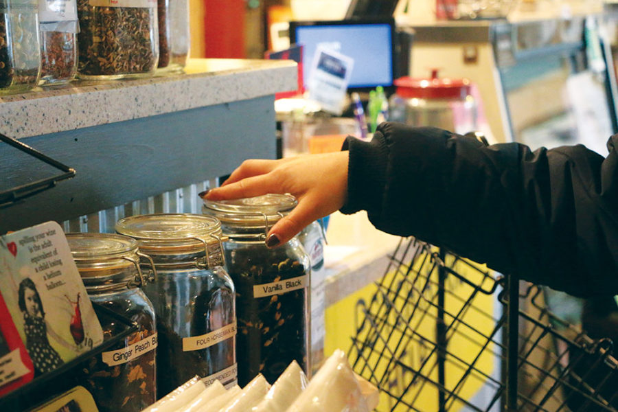 COFFEE CHOICES: Senior Mallory Cole twists the lid of a coffee jar at Soho Cafe. Many students currently go to Soho after school to study.