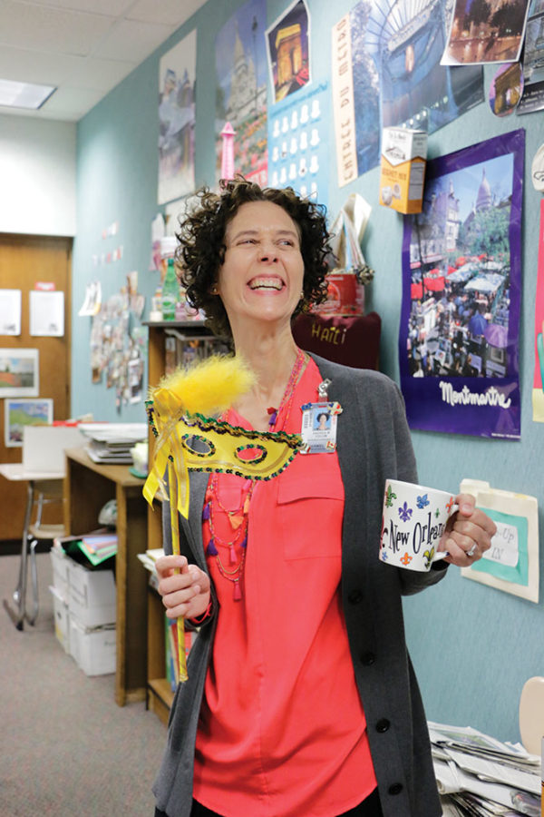 MARDI GRAS MASKS: Andrea Yocum, French teacher and world language department chairman, presents a mask for Mardi Gras and a New Orleans mug, where Mardi Gras originates. Most French classes at CHS celebrate Mardi Gras each March to experience the culture of New Orleans, the primary francophone region in the United States.