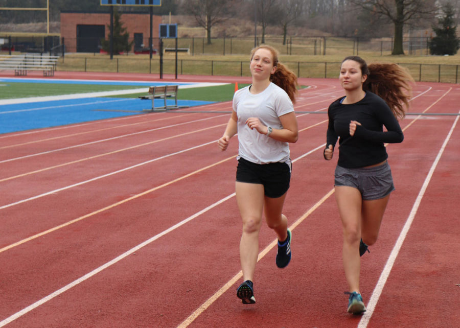 Pushing forward: Yael Kiser and Mia Bruder, track athletes and sophomores, jog to warm up for their training. By running together, the two athletes motivated each other to keep running.