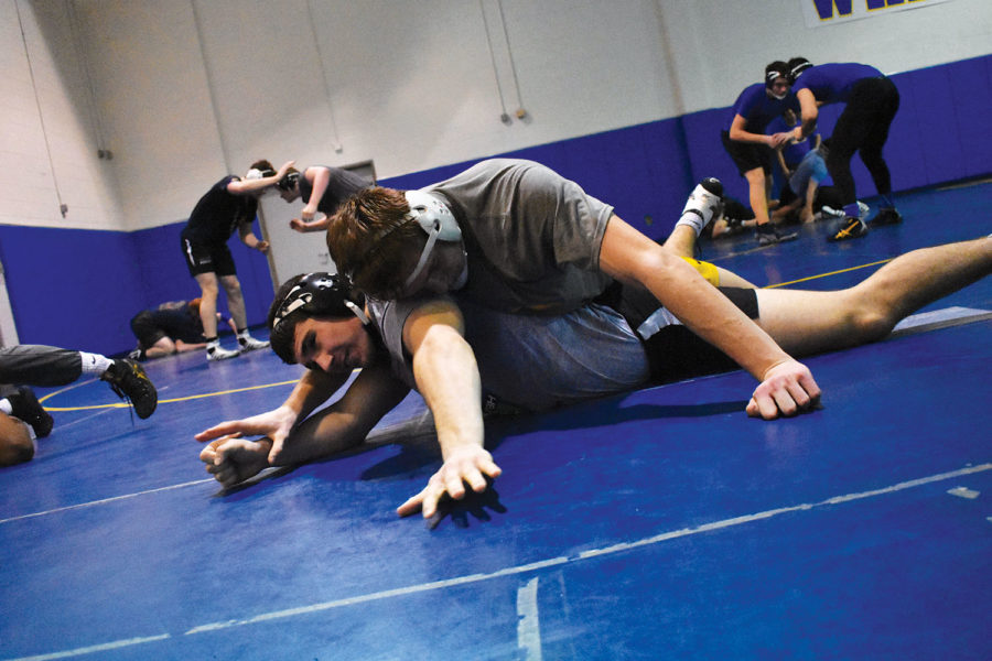 Layering basics: Wrestler and junior Jackson Mitchell gets taken down by wrestler and junior Garret Sharp in top drilling position. The position allowed Mitchell to have the advantage.