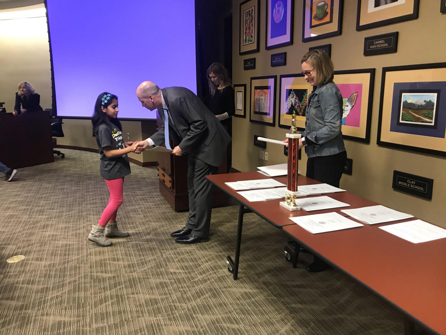 Superintendent Michael Beresford hands an award to a Science Bowl elementary school member during a school board meeting on Feb. 12. The award was intended to recognize the Collegewood Elementary School Science Bowl team for winning the Indiana state championship.
