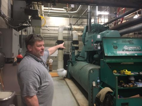 Maintenance worker Fred Napier points to one of the school's boilers. The maintenance department is currently working on preparing the school's coolers for the upcoming warmer weather and they have an outside company helping them.
