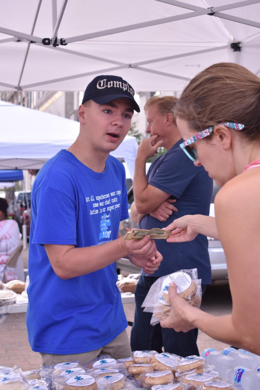 Caiden Wetherald, No Label at the Table Food Co. employee and junior, takes money from a customer at the farmer's market. According to Shelly Henley, owner and founder of No Label at the Table Food Co., the bakery's mission is to provide job skills training for people on the autism spectrum.