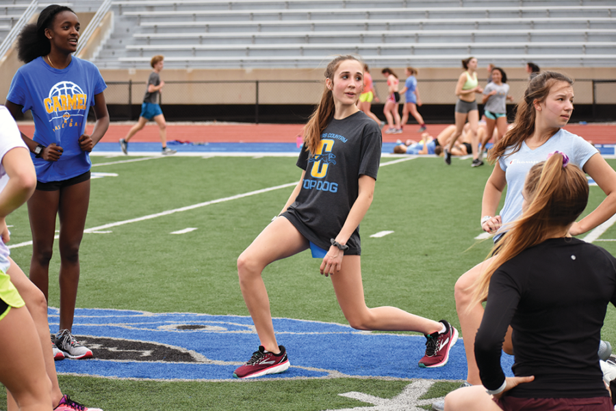 STRETCHING OUT:  Abby Grogan, varsity runner and sophomore, warms up before a practice. Grogan said while the cut was small, it has shifted the team composition.