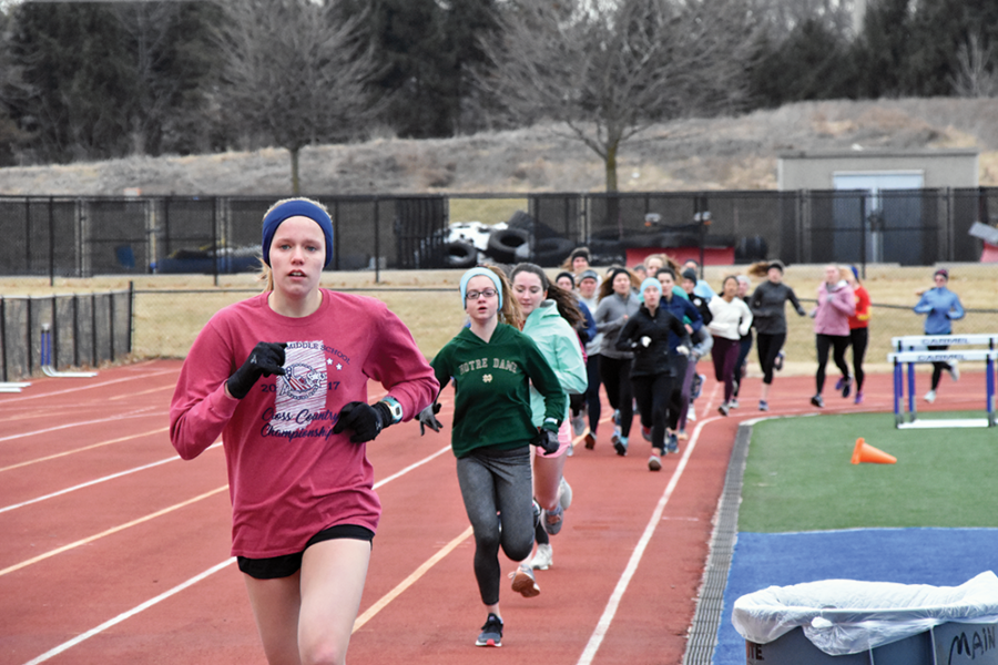 GETTING AHEAD: Runners warm up during a track practice. Head Coach Aaron McRill said the new times keep runners accountable.