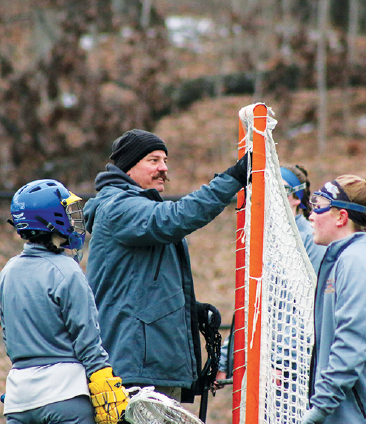 Joshua Miller, new  wom- en's lacrosse head coach,  helps adjust the net at Murray Stadium before a game on March 7. Though he may have a different approach to coaching than Hettiger, he said that few changes will be made to the team, allowing for a smooth transition.