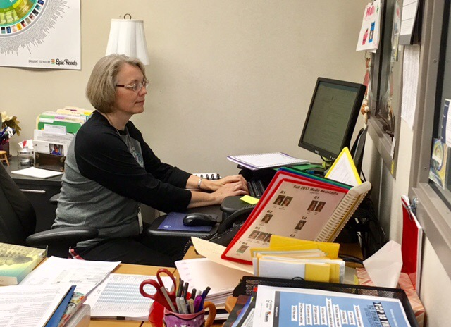 Terri Ramos, department chairperson for media and communications, looks at papers on her desk. Ramos said the media center always has something new for people to learn about.