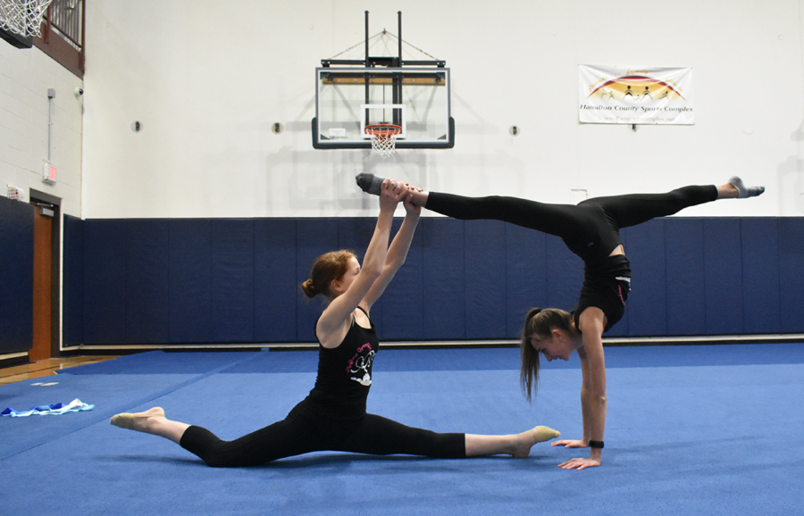 Sophia Gilliam, Folkins teammate and freshman, balances her in the middle of a skill.