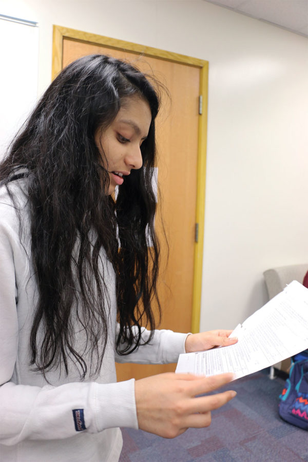 NEW MARKET: Sanjana Prasad, marketing student and sophomore, reads from her DECA paper. Prasad said she researched  about advertisements.