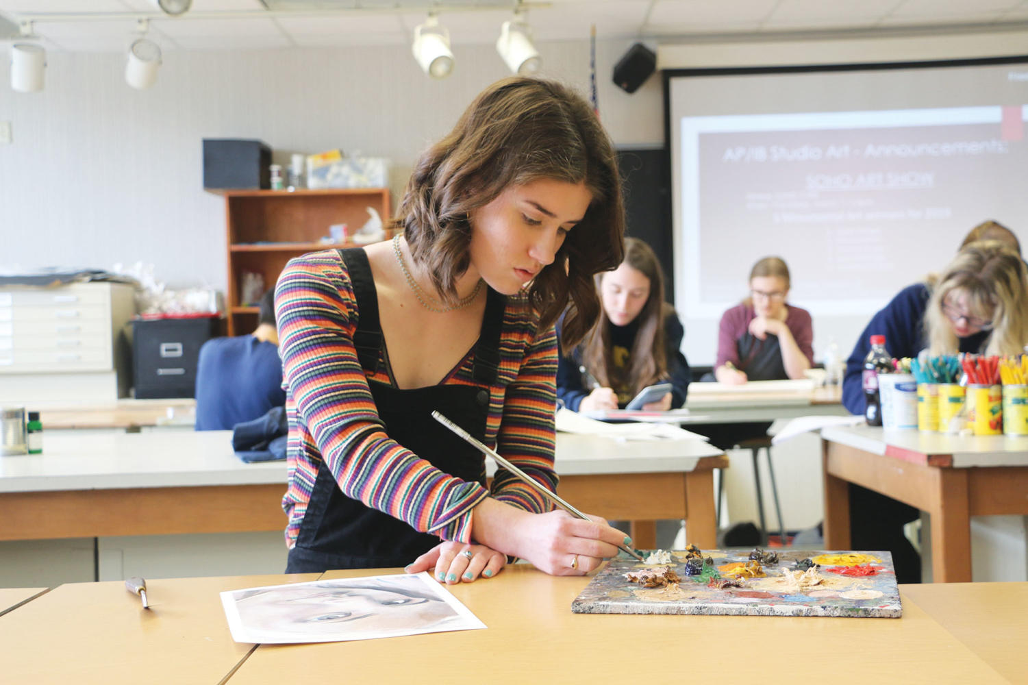 COLORING IN THE CANVAS: Sydney Remble, art student and senior, works on her painting during her class period. Remble said although she will not major in art, she hopes to incorporate it in her future.
