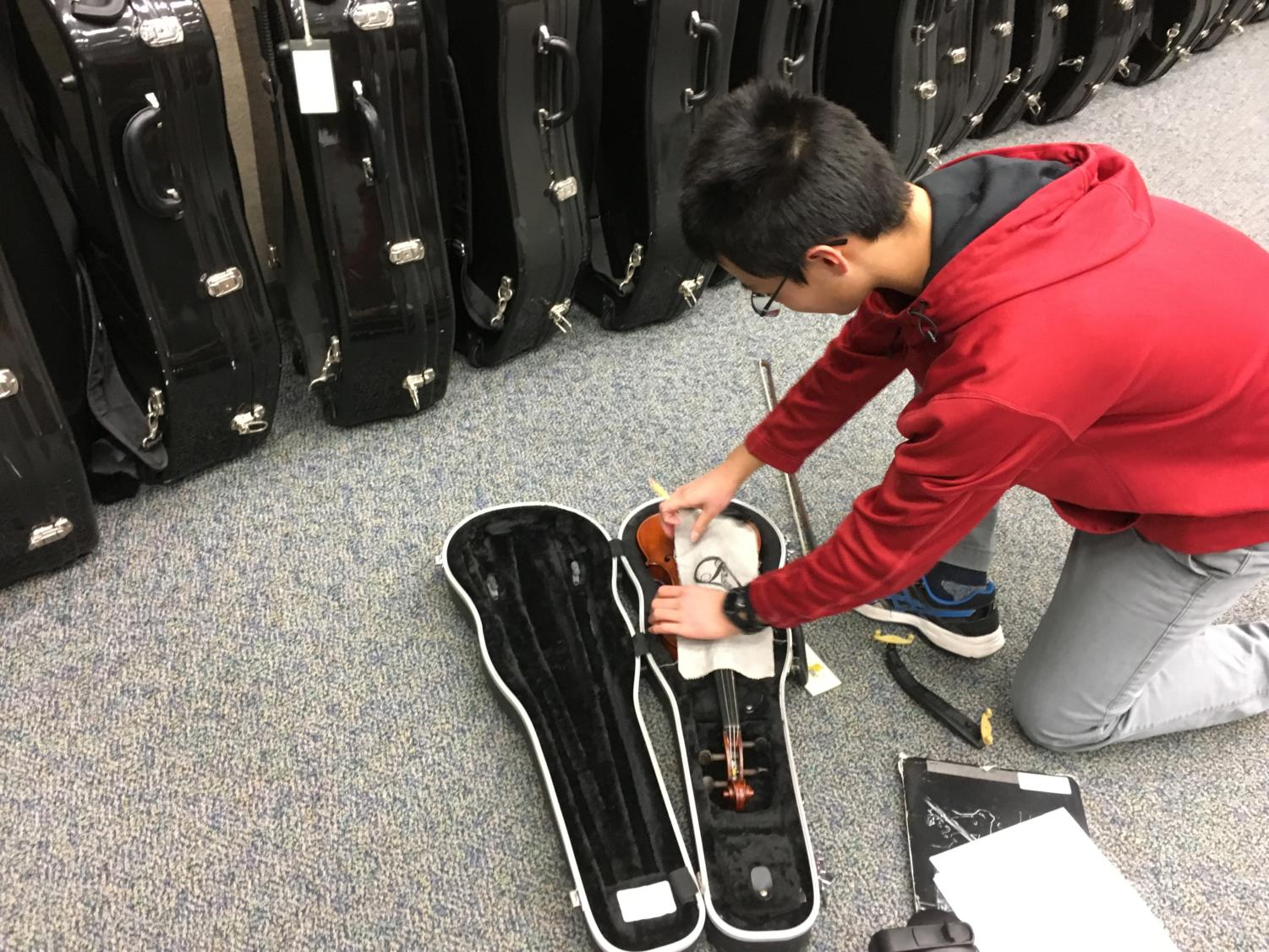 """Edward Dong, member of Philharmonic Orchestra and sophomore, packs up his violin at the end of the day. He said he has recently been preparing for the ISSMA (Indiana State Music Association) Competition and has benefited from the new practice recordings. """"ISSMA is basically our main priority now,"""" Dong said."""