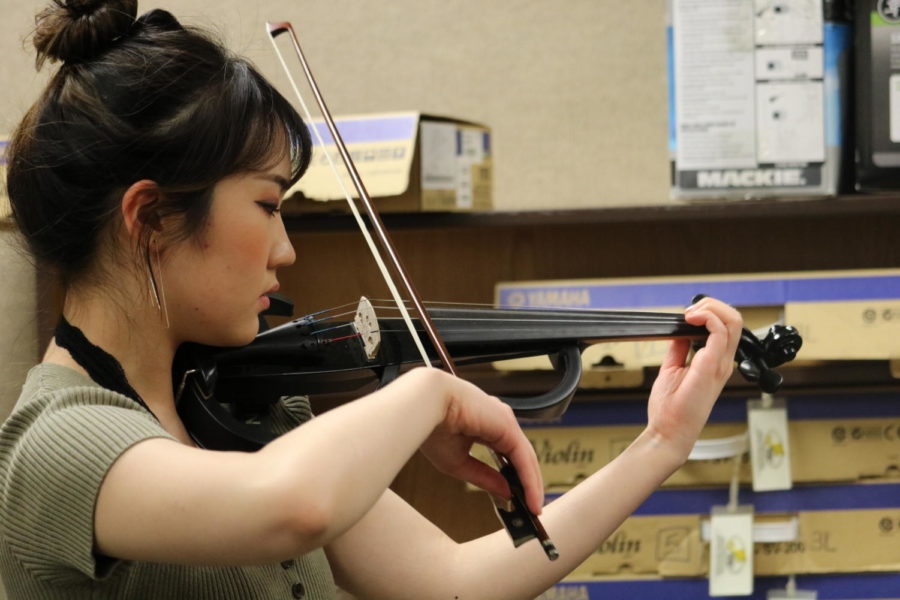 "Jiwon Yu, club president and junior, practices the club's latest music. The Carmel Electric Ensemble is preparing for the upcoming April concert, and they have been meeting more often to better their playing beforehand. Yu said, ""We are working on the rhythms and intonations (individually) because we are going to sight read for the next rehearsal."""