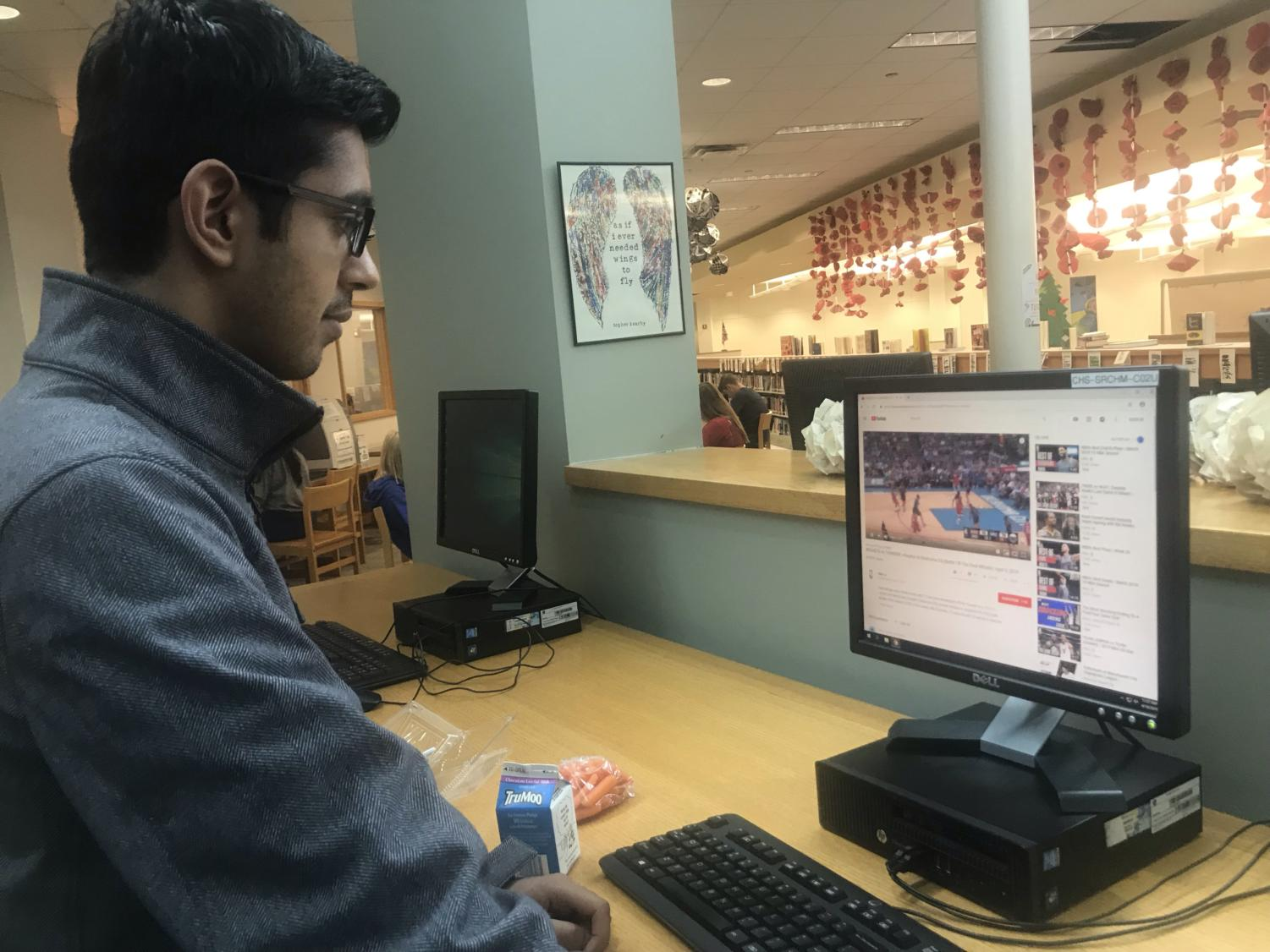 Senior Sumeir Ahmed watches a game of basketball during period B3. Ahmed said he was previously completing his math homework.