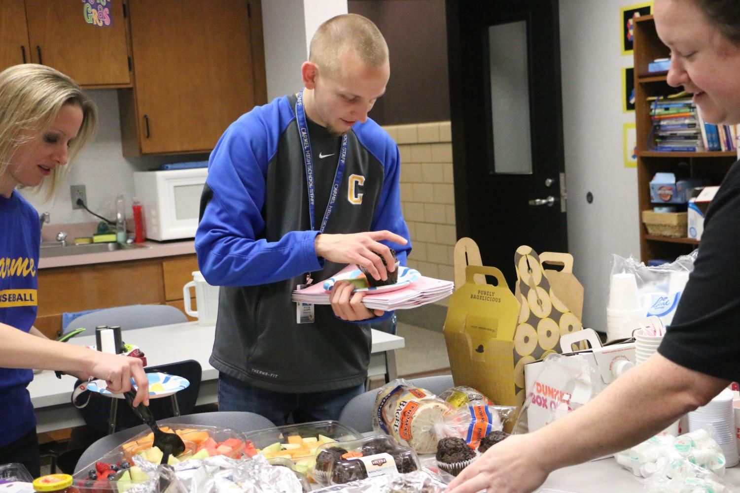 Breakfast Muffin Math teacher Kyle Cluver gets food from a breakfast event hosted by Do Something Club. The math department was awarded a free breakfast for collecting the most canned food for SENSE Charter School