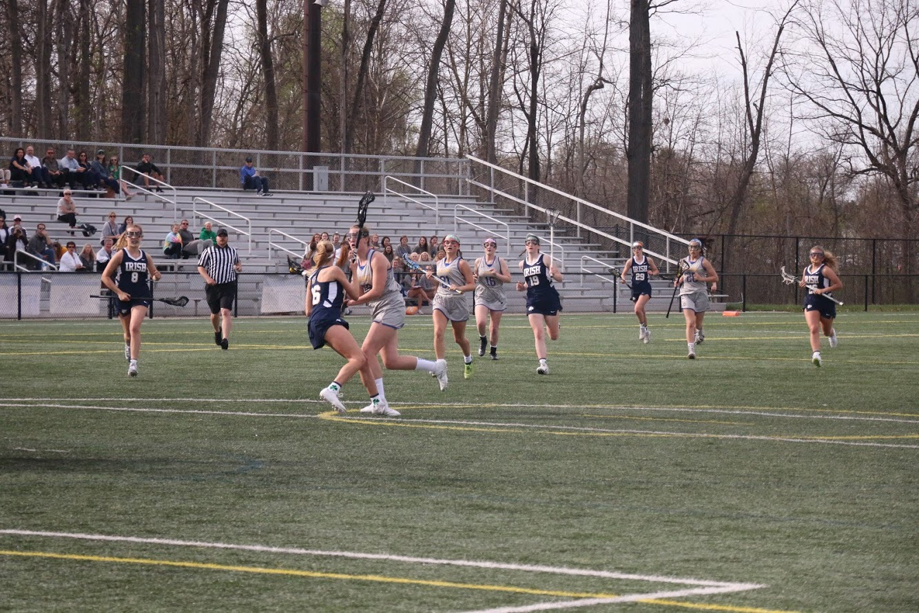 Mary Rose Ramsey, women's lacrosse player and senior, runs toward the goal with the ball as lacrosse team players follow. The team won against Cathedral 13-9.
