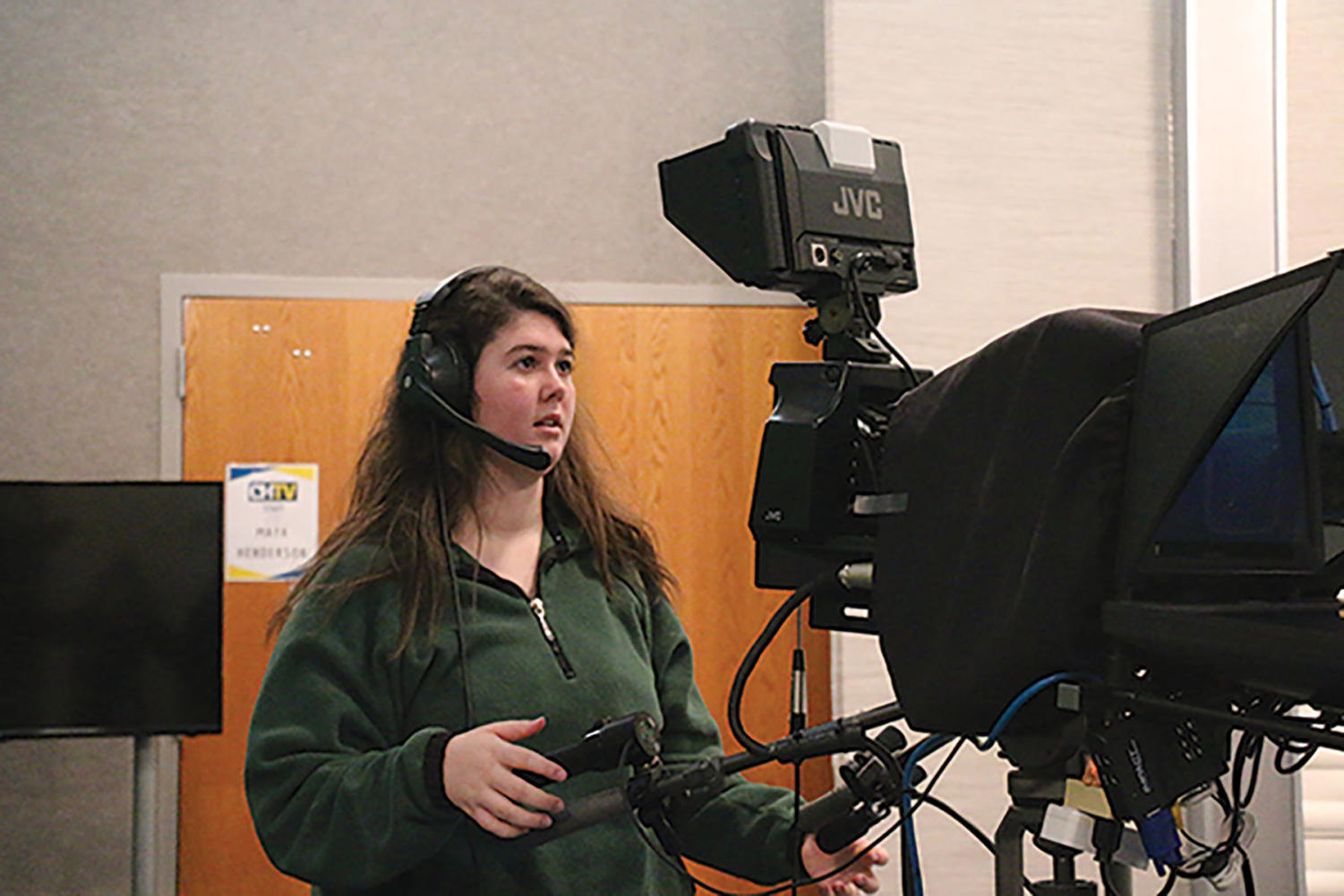 Maria Saam, CHTV Director and senior, adjusts the camera angle during the morning SRT show. Saam is one of the main directors and in charge of stage setting, lighting and audio  cuts during  the show.