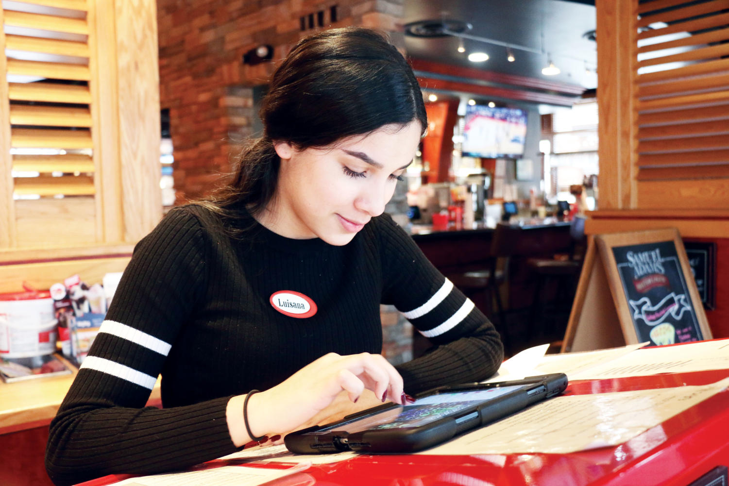 MAKING MONEY: Senior Luisana Rodriguez checks how many seats are available in Red Robin. Rodriguez has worked at Red Robin for a little less than a year. She said that her family sends money over to their relatives in Venezuela to help make their lives easier.