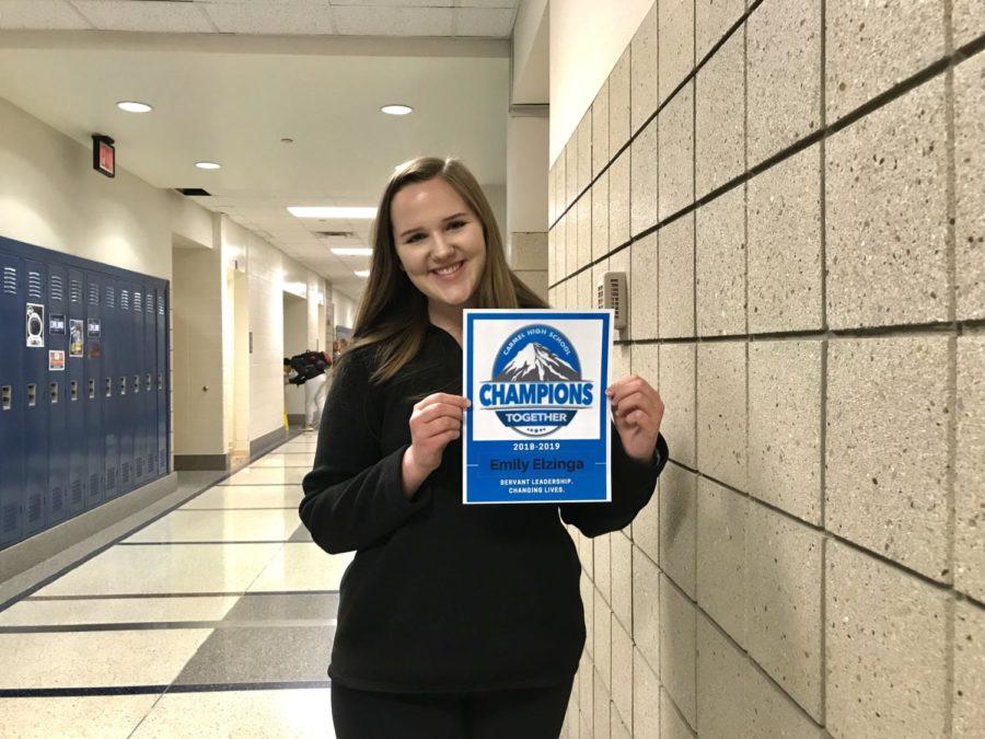 Co-president and senior Emily Elzinga holds her Champions Together locker sign. She said,