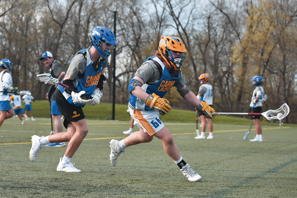 PLAY BY PLAY: Senior Joe Pendl and sophomore Daniel Seed, varsity lacrosse players, race for the ball during a speed drill. Meachum explained that strategy and speed were important for success.