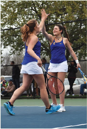 """HIGH-FIVE: Senior Franny Werner high-fives her doubles partner, sophomore Katelyn Conley, during a match against Cathedral. CHS lost the match 2-3; this was their first loss in three years. Werner said, """"Being a senior on the team means you have to be a leader, and you help motivate everyone to play, including yourself."""""""