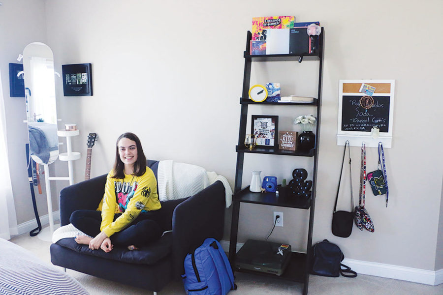 Sophomore Ashley Elmore's sits on the loveseat in her room. Elmore said she thinks different elements of her room, such as her mirror and loveseat, are interesting pieces that add to the aesthetic of her room.