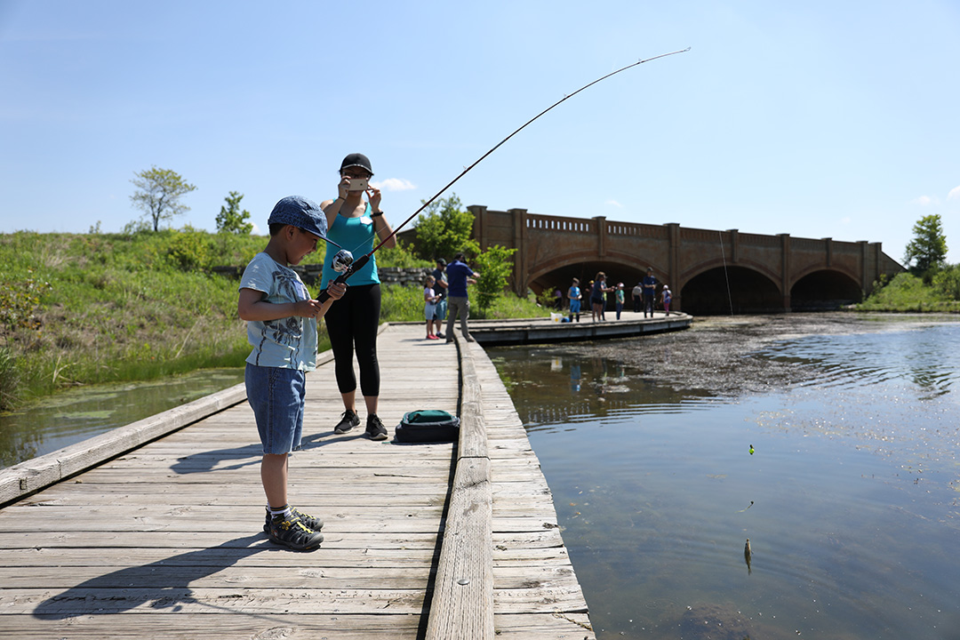 Family Learn to Fish participant catches a fish while his mom watches nearby. The Department of Natural Resources scheduled the event on a Free Fishing Day, which means that anglers don't need a license to fish the state's public waters. Participants also learned about ethics during the event, so they caught and released the fish.