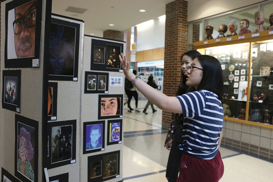 Senior Jessica Qu and junior Minjeong Kim point at a particular piece of artwork. Qu said she applied for a curator position because she is interested in art and design.